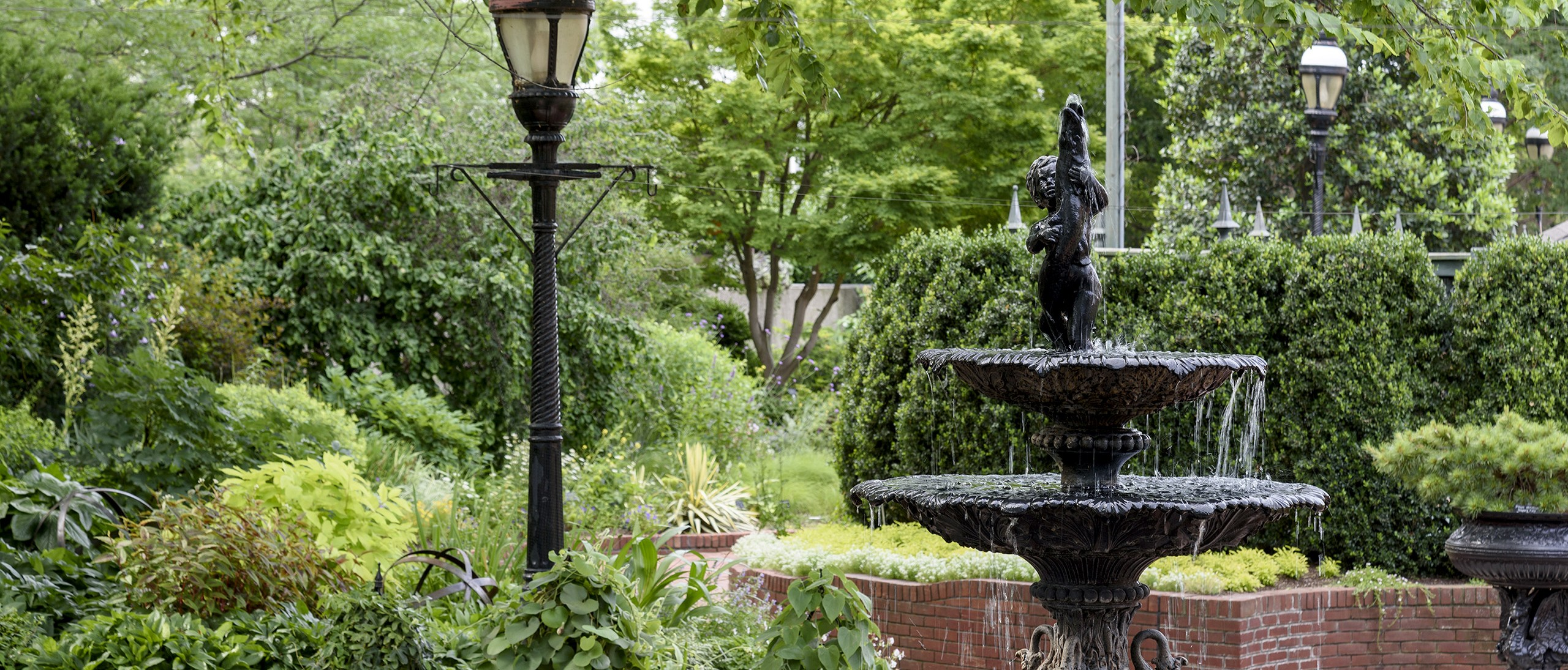 Cast iron three-tiered fountain with bird motif framed by raised brick beds planted with varying shades of green