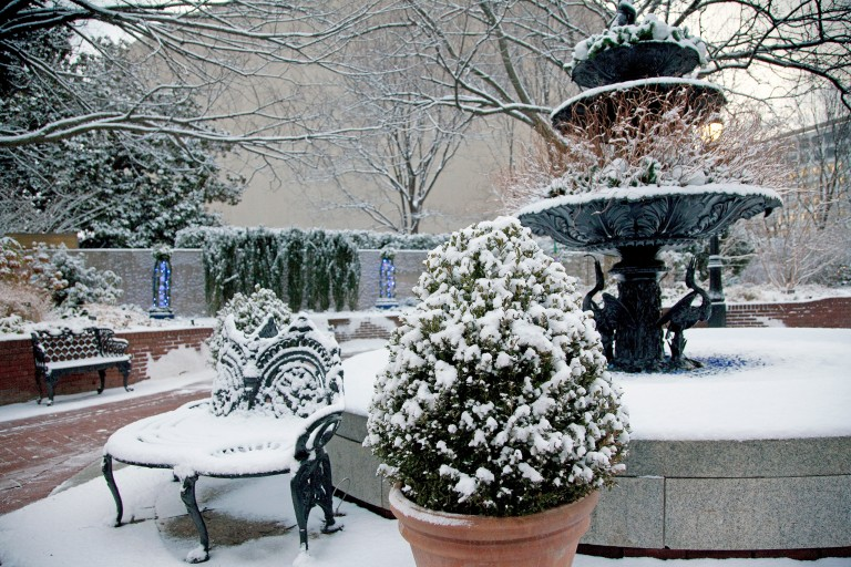 Cast iron three-tiered fountain and benches covered in snow