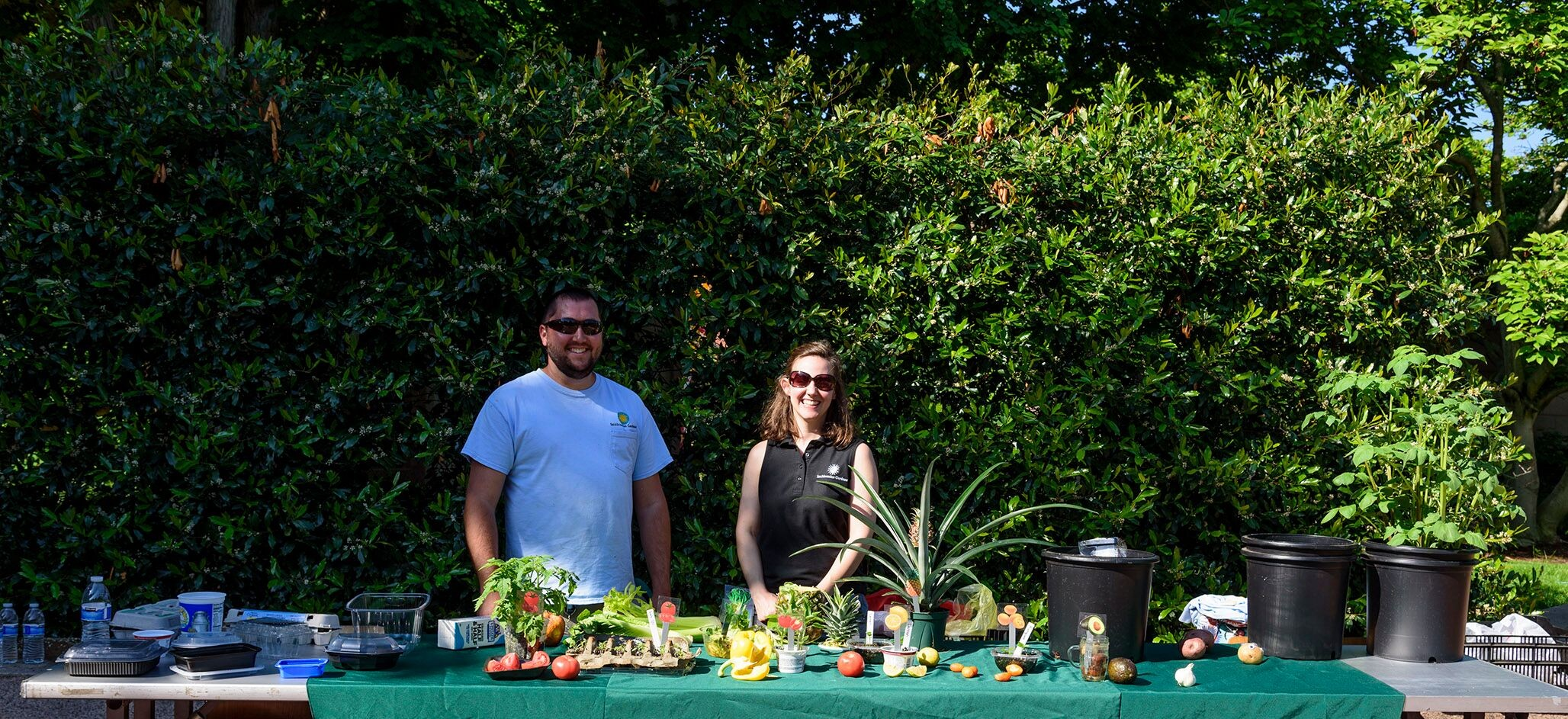 Two Smithsonian Gardens staff members stand behind table of plants grown from food scraps