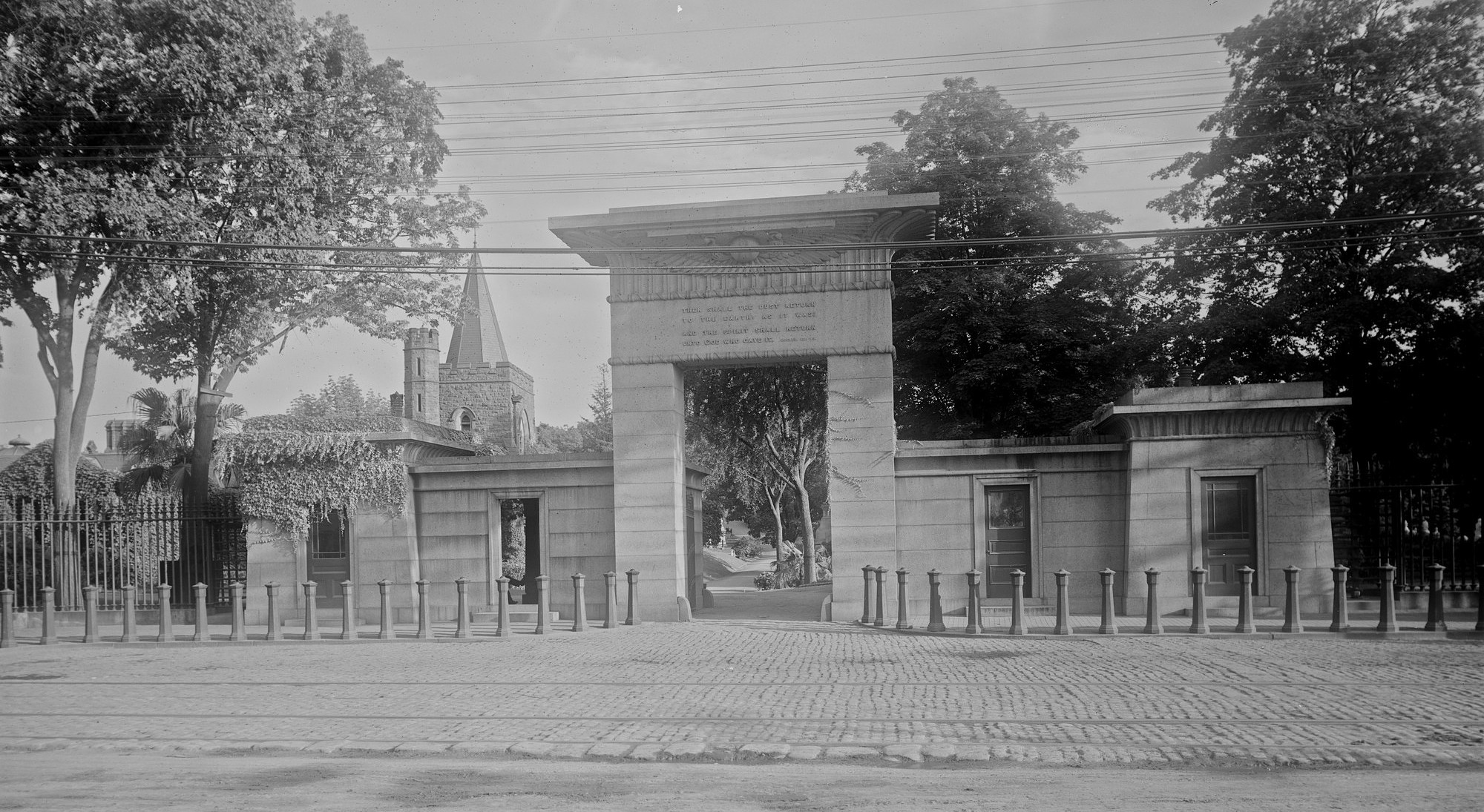 Black and white photo of cemetery gates.
