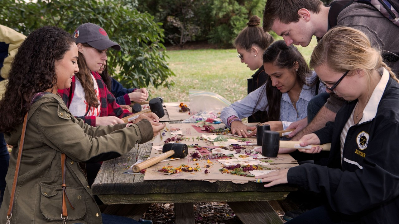 Young adults work on flower pounding craft at picnic table
