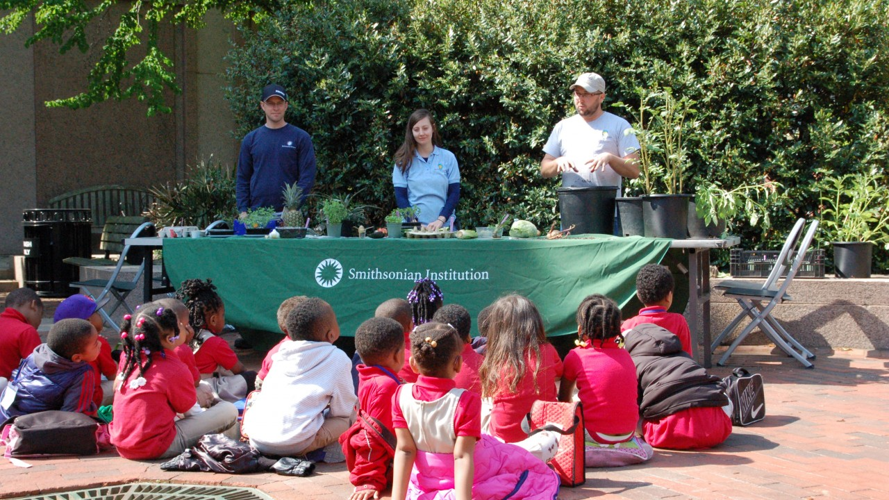 Children sitting on walkway watching plant demonstration