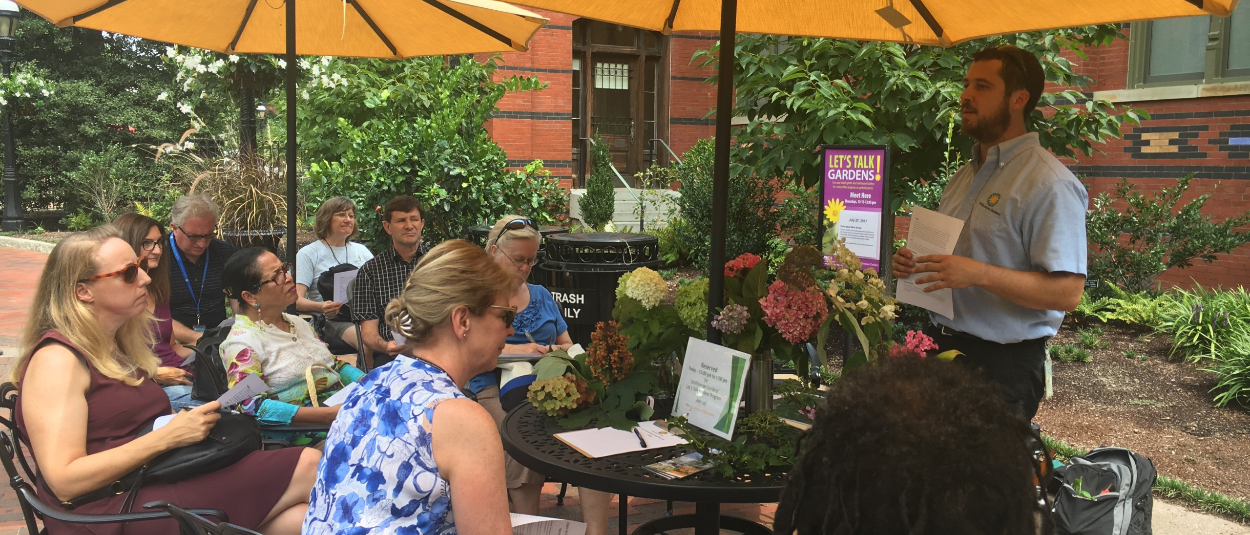 Horticulturist teaching seated attendees about hydrangea care under yellow shade umbrellas