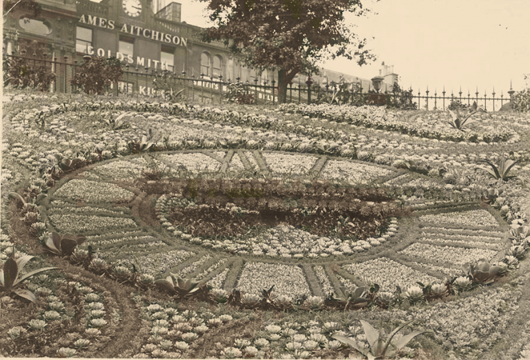 Vintage image of large clock created through flower plantings on the side of a hill