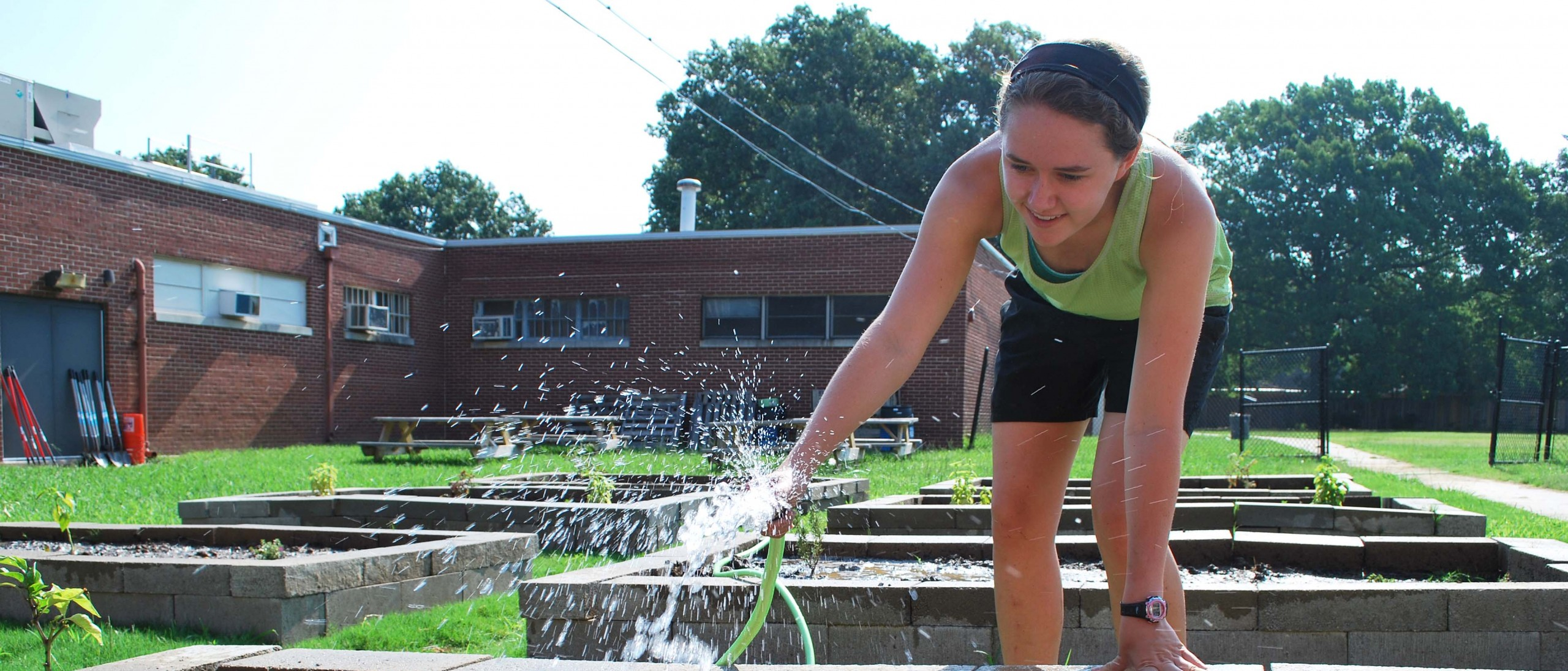young woman watering one of several raised garden beds behinf brick school building