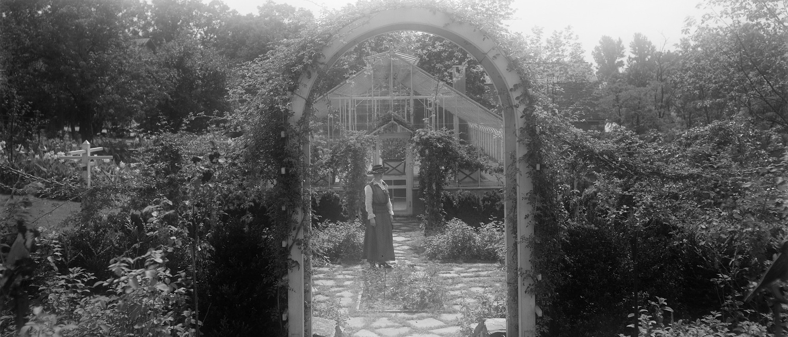 Woman in broad-brimmed hat standing behind a vine-covered archway